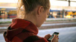 Mujer de espalda usando su telefono mobil